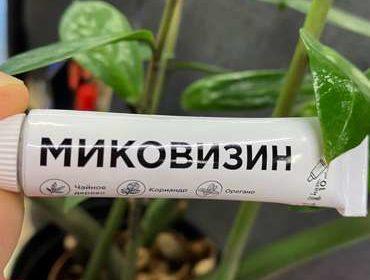 Тюбик крема Миковизин на фоне цветка.